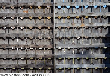 A Wooden Fencing Made Of Old Wine Racks. The Wooden Enclosure With Rows Of Round Holes.