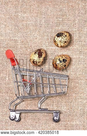 Quail Eggs Against The Background Of A Linen Napkin Fly Out Of A Grocery Cart. Small Grocery Cart. Q