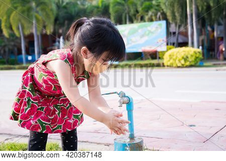 Cute Girl Wearing Orange Cloth Face Mask Was Washing Her Hands From Faucet With Clean Water In Publi