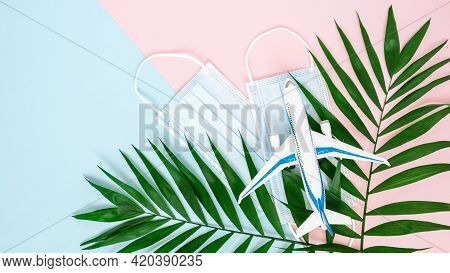 Airplane, Medical Masks And Palm Leaves On Combined Pink And Blue Background With Copy Space. Minima