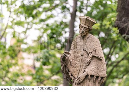 Monument In The Garden Of Brno Castle. Stone Monument To A Man On The Background Of Spring Trees.