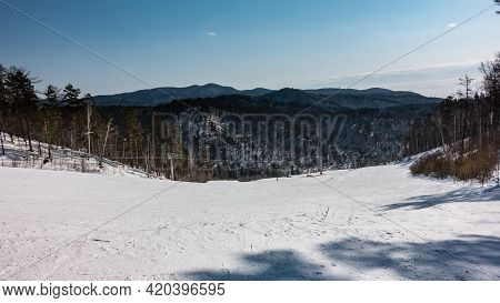 A Chairlift Runs Over The Snow-covered Mountain Slope. Ski Tracks In The Snow. Wooded Mountain Range