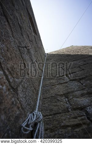 Rope On Stone Wall Of Castle. Escape From Medieval Castle, Tourist Attractions. Old Medieval Archite