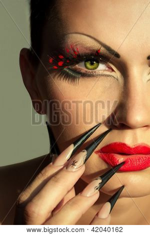 Woman face with creative fashion makeup and manicure in the sunlight