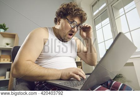 Surprised Shocked Funny Fat Man In Pajamas Reads Amazing News On Laptop