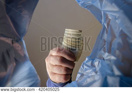 The Hand Throws Money In The Trash. A Man Is Holding Several Russian Rubles Over The Trash Garbage C