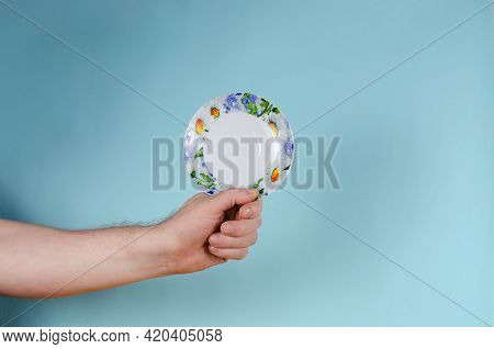 Man Holding White Saucer With Painted Flowers. Ceramic Saucer Brightly Decorated In Blue And Yellow