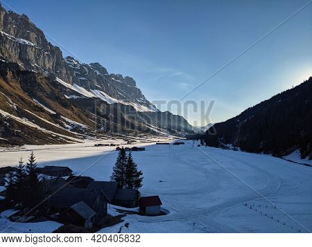 Urnerboden. Cross-country Ski Run And Pass Road In The Picture With High Mountains On The Sides. Uri