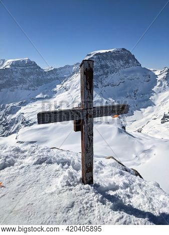 Summit Cross On The Gemsfairenstock With A View Of The Piz Russein Toedi. Urnerboden. Winter Mountai