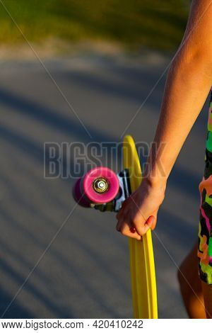 Defocus Girl Holding Yellow Penny Board. Back View. Youth Hipster Culture. Close-up Child Hands Hold