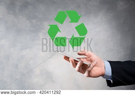 Businessman In Suit Over Dark Background Holds An Recycling Icon, Sign In His Hands. Ecology, Enviro