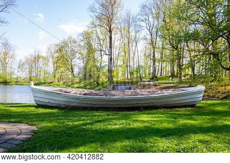 White Wooden Boat In The Park, Next To A Pond That Has Been Turned Into A Flower Bed. The Boat Is Fu
