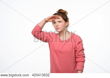 Portrait Of A Curious Young Girl In Pink Casual Sweatshirt Looking Far Away With Hand At Her Forehea