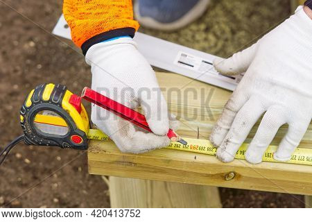Diy Carpenter Marks A Piece Of Wood. Carpenters Hands In White Gloves And Tools For Precise Work