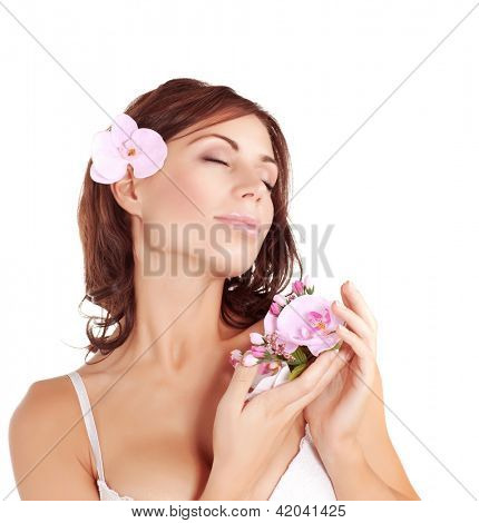 Image of cute brunette girl enjoying dayspa, closeup portrait of beautiful female with closed eyes relaxing in spa salon, pretty young lady with pink orchid flower isolated on white background