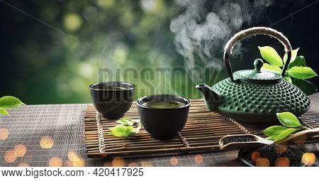 Japanese Tea - Hot Teapot And Teacups On Bamboo Mat