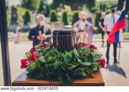 Funerary Urn With Ashes Of Dead And Flowers At Funeral.