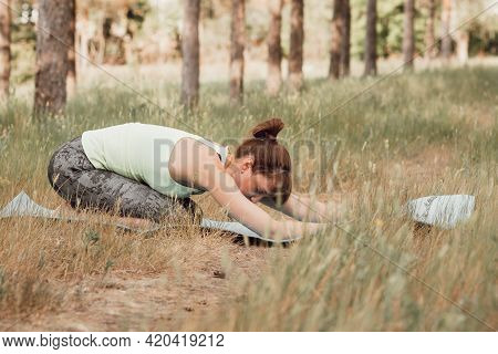 Sporty Woman Practicing Yoga, Stretching And Relaxation In Park Outdoors, Fitness In Nature