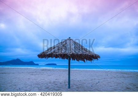 Umbrella Is On An Empty Beach In The Morning. Porto Santo Island, Madeira Archipelago, Portugal