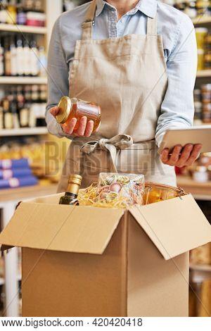 Close Up Of Female Owner Of Delicatessen Food Shop With Digital Tablet Preparing Online Grocery Orde