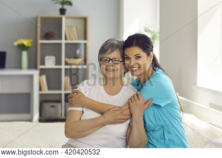 Happy Senior Woman Together With Her Home Care Nurse Or Caregiver Smiling At Camera