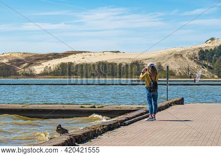 Nida, Lithuania - May 10 2021: Tourist Girl Taking Photos Of The Desert Dunes Of The Curonian Spit I