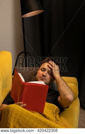 Male Reader Took Hand To Head Reading Detective Or Historic Novel At Comfy Couch