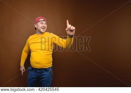A Positive, Overweight Man In Casual Clothes Throws His Index Finger Up In A Happy Gesture Having Fo
