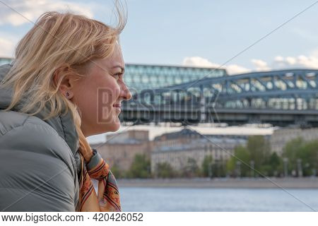 Blonde Middle-aged Woman In Profile Stands On Embankment And Looks At River Against The Background O