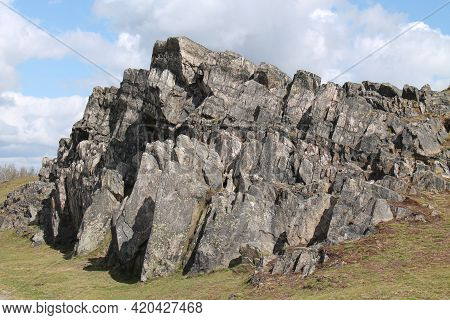 A Natural Large Rock Outcrop On A Countryside Hillside.