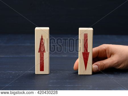 Female Hand Holds A Wooden Block With An Upward Arrow And Down Arrow. Concept Of Increasing Profit G