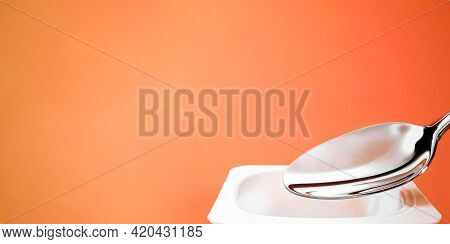 Yogurt Cup And Silver Spoon On Orange Background, White Plastic Container With Yoghurt Cream, Fresh