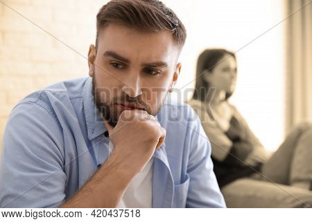 Unhappy Young Couple With Relationship Problems At Home, Focus On Man. Cheating And Breakup