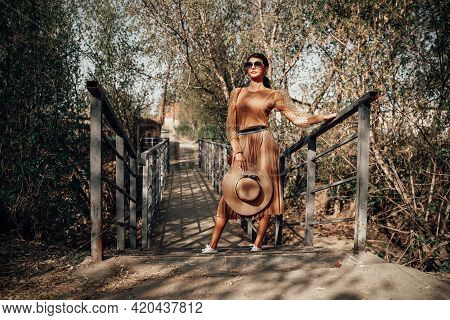 Stylish Lady In A Beige Outfit And A Hat With Sunglasses. Details Of The Everyday Look. Fashionable