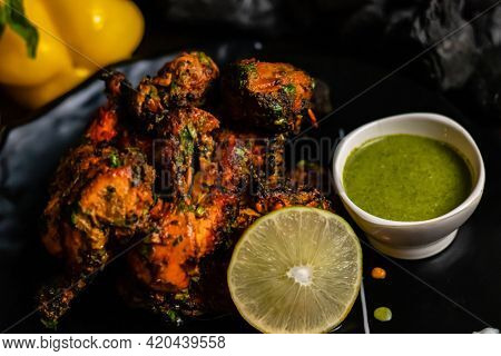 Close Up Shot Of Delicious Roasted Chicken With Lemon, Green Spicy Sauce And Charcoal In The Backgro