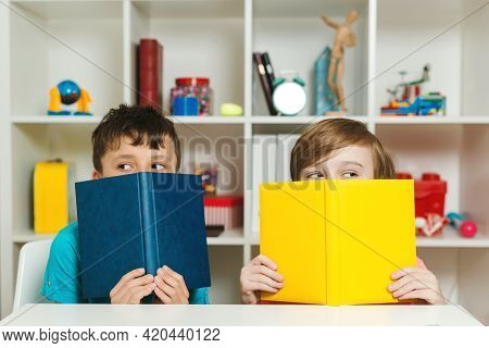 Two School Boys Hiding Behind Book At Classroom. Happy Friends Having Fun Together After Lesson. Edu