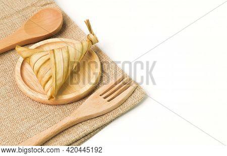 Ketupat Palas Or Rice Dumpling On Wooden Plate. Ketupat Palas Is A Natural Rice Casing Made From You
