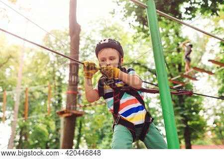 Cute Boy Climbing The High Rope Course In Adventure Park. Kid In Safety Helmet, Extreme Sport. Summe