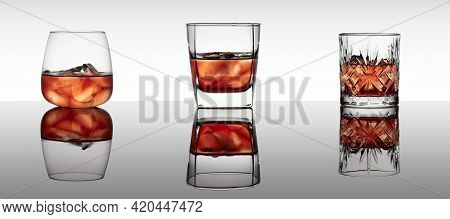 Three Various Glasses Of Whiskey With Ice On A Black Reflective Background. Natural Reflection. Save