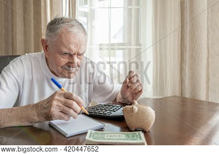 Old Man With A Pencil Counts Pennies From The Pension Fund Sitting At A Table In The Room. Worried E