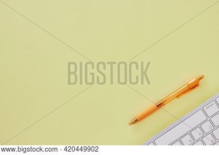 Top View Or Flat Lay Modern Office Desk Or Office Table With Computer Keyboard And Orange Pen. Yello