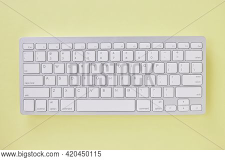 Top View Or Flat Lay White Wireless Computer Keyboard On Pastel Yellow Office Desk Or Office Table B
