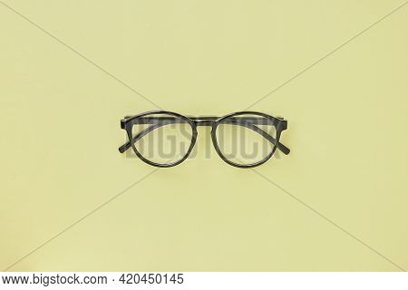 Top View Black Glasses On Pastel Yellow Minimalist Background