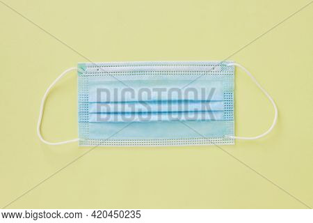 Top View Or Flat Lay Blue Face Mask On Light Yellow Minimalist Background