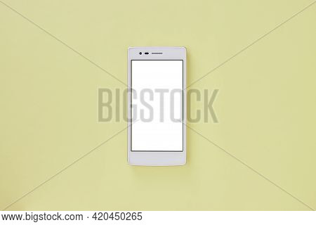 Top View Or Flat Lay White Smartphone Or Mobile Phone Mock Up On Pastel Yellow Office Desk Or Office