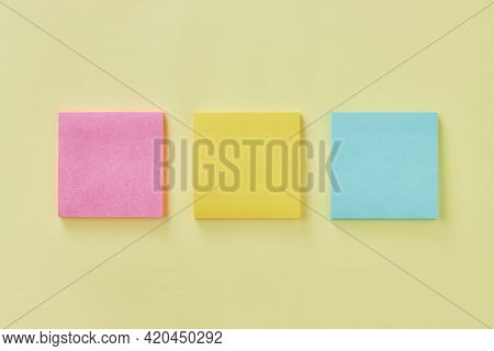 Top View Or Flat Lay 3 Color Stick Note Or Note Pad As Pink,yellow,turquoise On Office Desk Or Offic