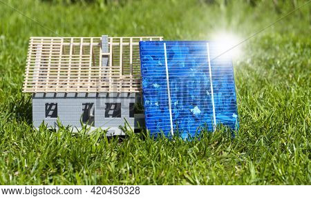 Solar Energy Cells With Glas Globe And Miniature House In Green Grass