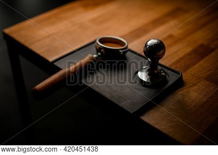 Portafilter With Tamped Coffee And Temper Lying On Black Stand On Wooden Table
