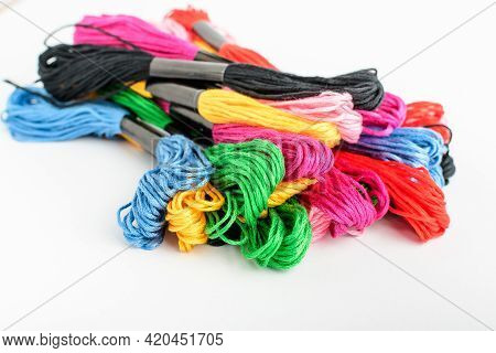 Many Mixed Vivid Colored Sewing Threads For Embroidery Displayed In A Circle Isolated On A White Tab