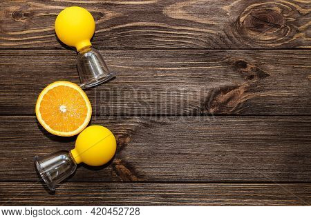 Vacuum Massage Anti-cellulite Cups On A Wooden Background With Orange. Self-massage For Healthy Skin